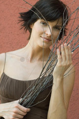 Woman holding dry branches  smiling at camera