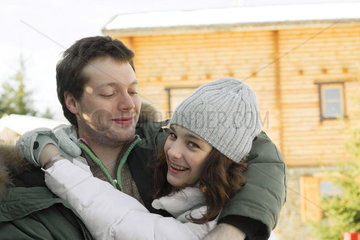 Teen girl hugging young man  looking over shoulder at camera  laughing
