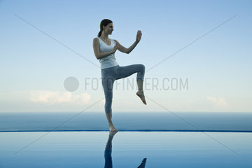 Woman practicing Tai Chi Chuan on edge of infinity pool