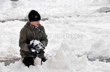 Junge spielt im Schnee