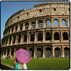 Woman holding a paper umbrella in front of the Colosseum  Rome  Italy