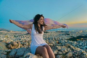 Eine Frau im Sonnenuntergang breitet lachend ein buntes Tuch vor dem Panorama Athens aus