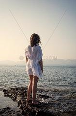 Frau steht am Meer