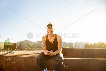 Junger Mann im Park mit Smartphone