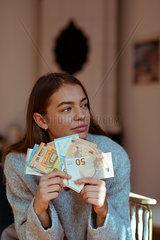 Junge Frau haelt Euro-Geldscheine in der Hand