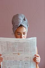 Junge Frau liest Finanzteil der Zeitung