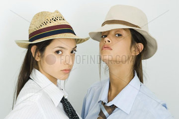 Two young female friends wearing hats and ties  both looking at camera