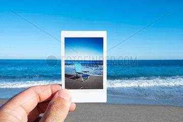 Mann haelt ein Foto am Strand