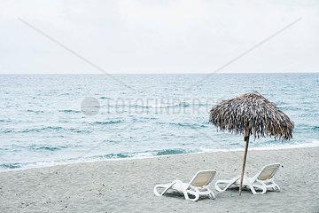 Zwei Sonnenliegen und Sonnenschirm am Strand