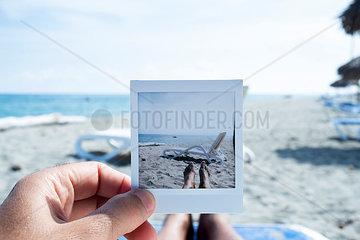 Mann mit Foto am Strand