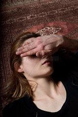 Hand verdeckt das Gesicht einer Frau die am Boden liegt