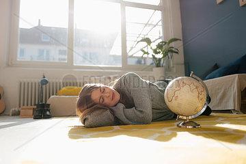 Junge Frau mit Globus in ihrer Wohnung