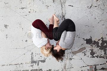 Zwei Frauen liegen in Herzform gegenueber auf dem Boden