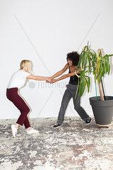 Zwei juneg Frauen zeihen sich gegenseitg an einer Zimmerpflanze
