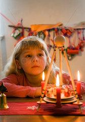 Berlin  Deutschland  Maedchen betet vor einer Weihnachtspyramide