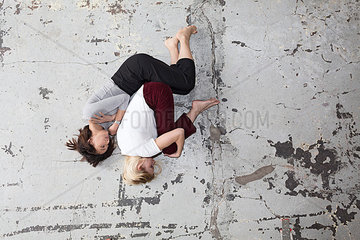 Zwei Frauen liegen in Empryostellung auf dem Boden