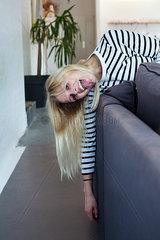 Junge Frau ist entspannt auf dem Sofa