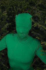Frau im gruenen Ganzkoeperanzug