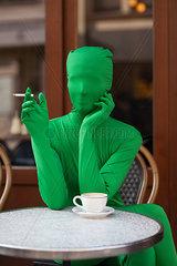 Person im Morphsuit raucht genuesslich im Café