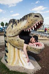 Junger Mann liegt in einem Dinosaurierkopf