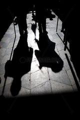 Sevilla  Spanien  Schatten von Maennern  die durch einen Mittelgang einer Kirche gehen