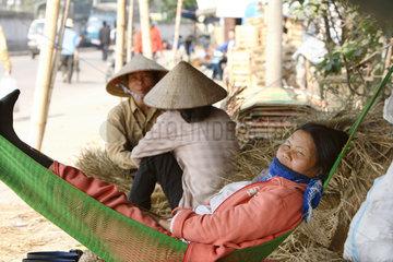 Ein Vietnamesin ruht sich an einer Strasse in einer Haengematte aus