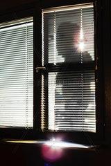 Silhouette eines Mannes mit Hut hinter einem Fenster