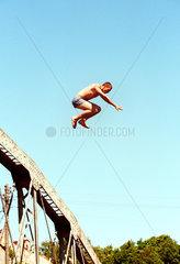 Jugendlicher springt zum Spass von einer Bruecke ins Wasser  Russland (Kaliningrad)