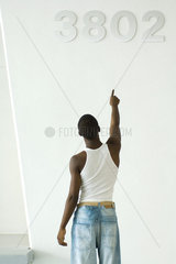 Teenage boy pointing at numbers on wall  rear view