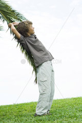 Boy leaning against palm branch  side view