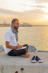 Spain. Man writing on a notebook during sunrise