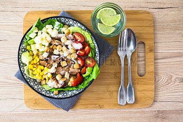 Bowl of Caesar salad with meat  corn and tomatoes