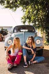 Two young women sitting outside at a vintage car