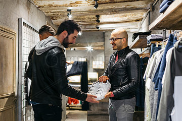Designer in modern menswear shop showing new shoes to man