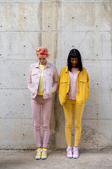 Two alternative friends having fun  wearing yellow and pink jeans clothes  looking down