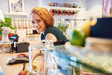 Portrait of smiling young woman with card reader at the counter in a cafe
