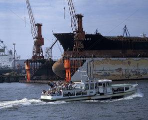 Hamburger Hafen  Frachtschiff im Schwimmdock der Schiffswerft Blohm + Voss  Touristenboot auf der Norderelbe