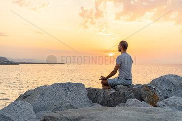 Spain. Man meditating during sunrise on rocky beach