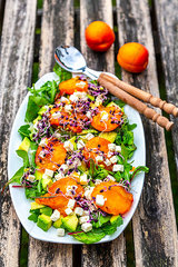 Green salad with fried apricots  avocado  feta cheese and radish sprouts