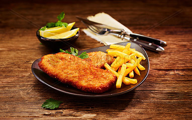 Pork escalope and French Fries on plate  lemon in bowl