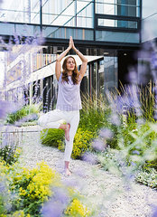 Woman practicing yoga in garden outsde office building