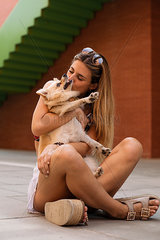 Smiling young woman sitting and kissing her dog