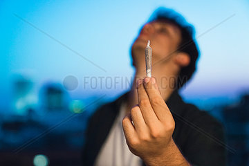 Young man holding joint