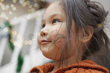 Portrait of little girl with paint strokes on her cheek