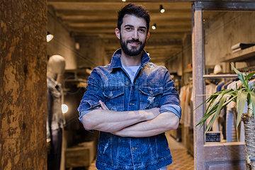 Portrait of smiling man wearing denim jacket in menswear shop