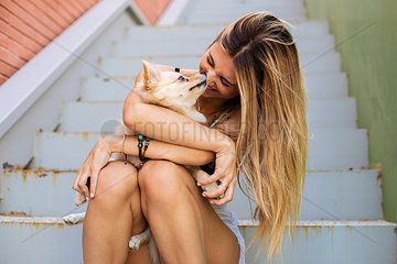 Smiling young woman sitting on stairs  holding her dog