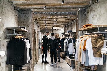 Three men standing in modern menswear shop