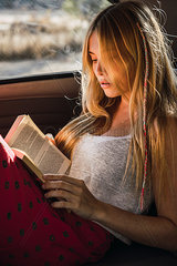Young woman sitting in a car reading book