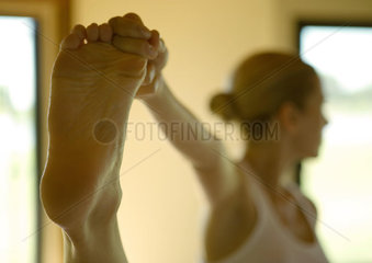 Woman standing  holding up foot