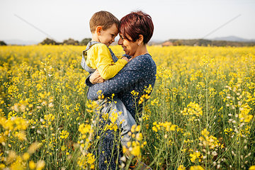 Mother standing with her little son in a rape field